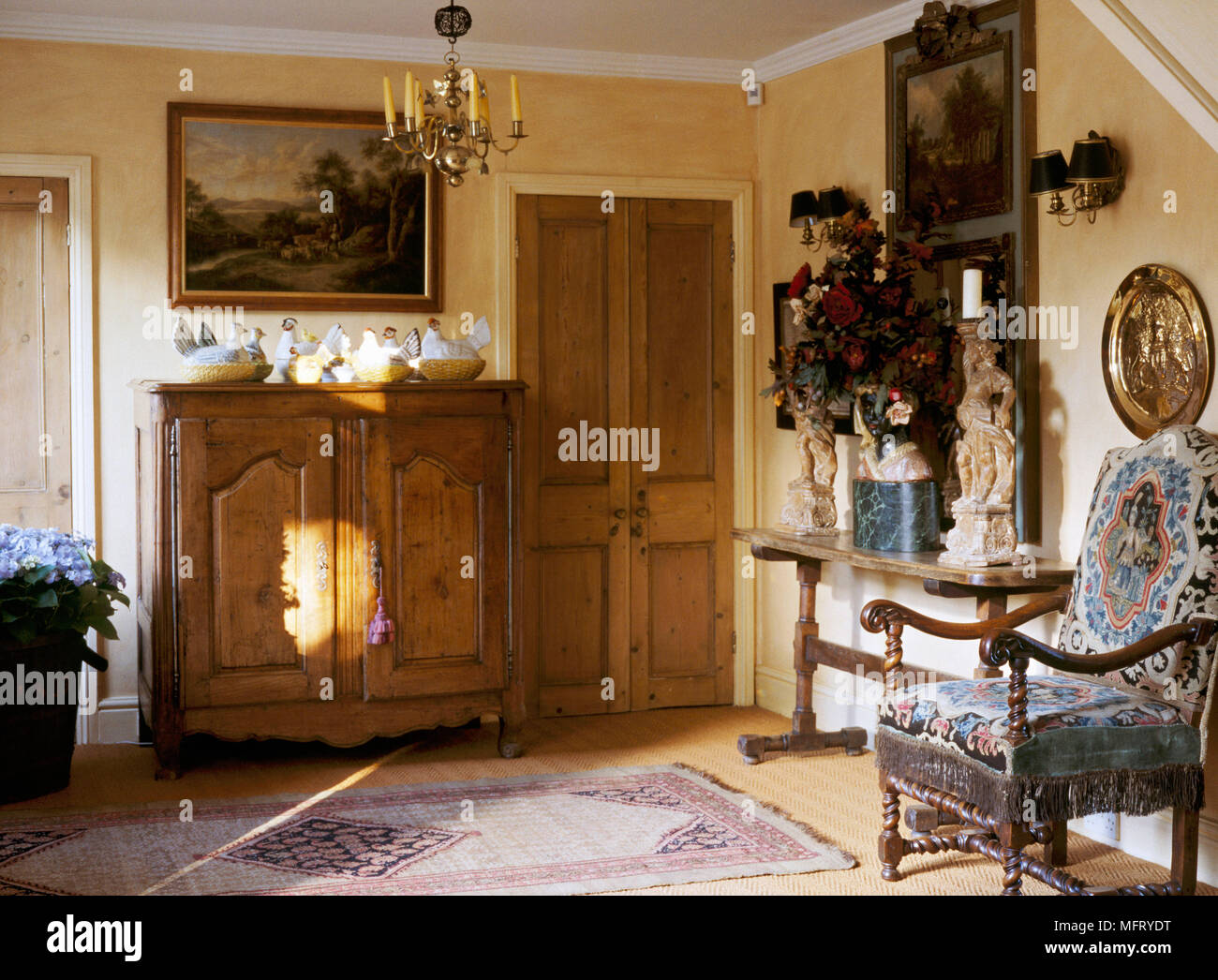 A traditional yellow entrance hall a pine wooden cabinet with collection of Staffordshire pottery hens  chandelier Jacobean style chair wood table Stock Photo