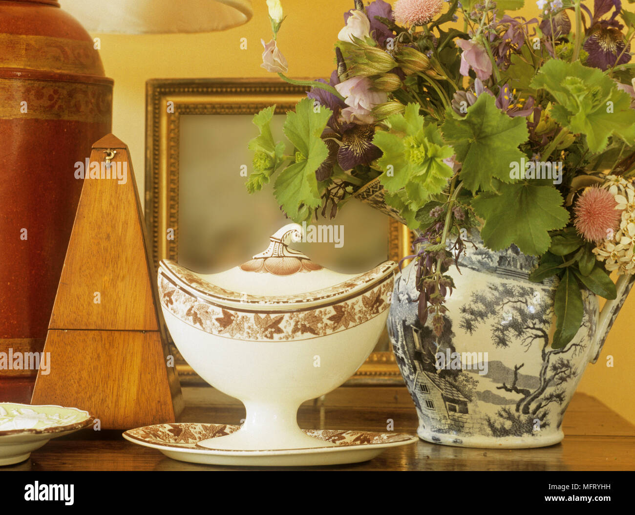 Detail of objects on wooden table including china jug with flowers and metronome. - Stock Image