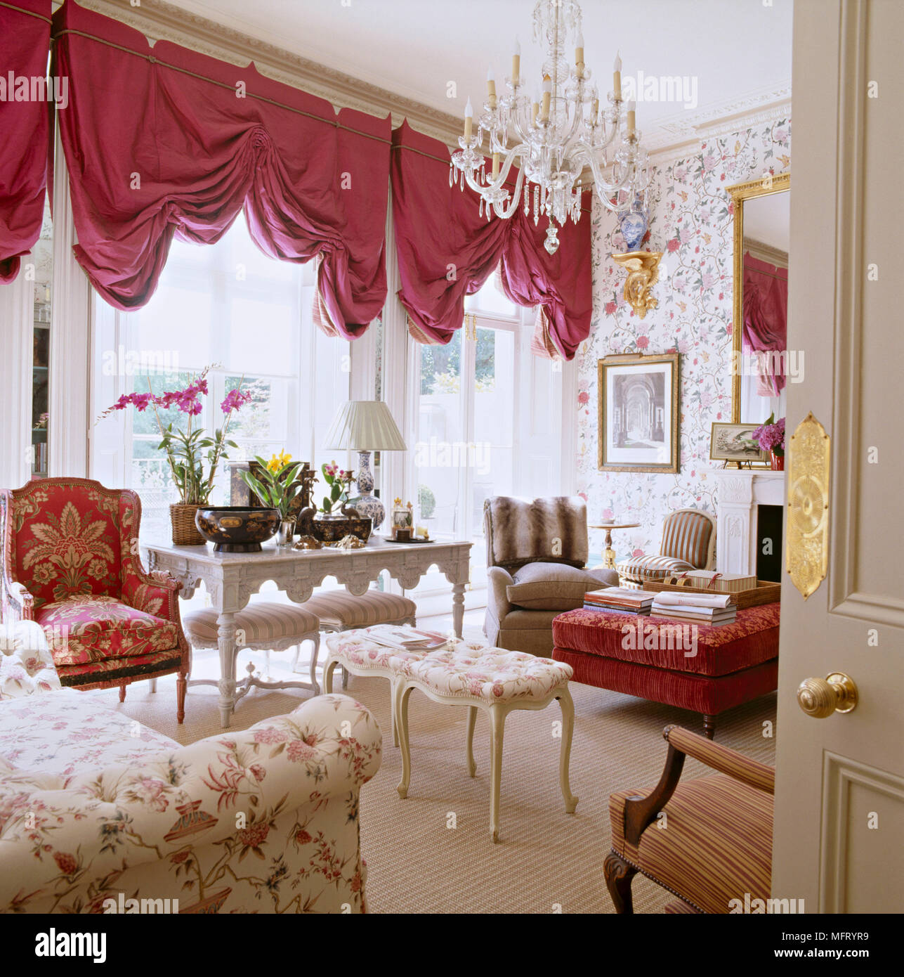 Sitting Room With Red Draped Curtains And Chendelier