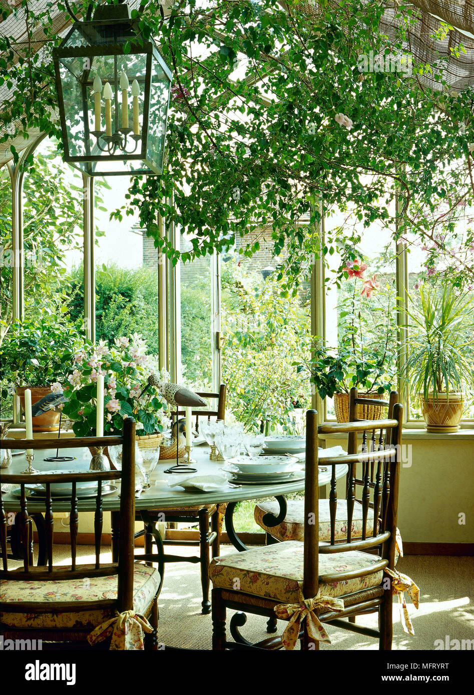 Traditional Conservatory Round Dining Table Wooden Chairs Indoor Plants Lantern Light Interiors Rooms Conservatories Stock Photo Alamy