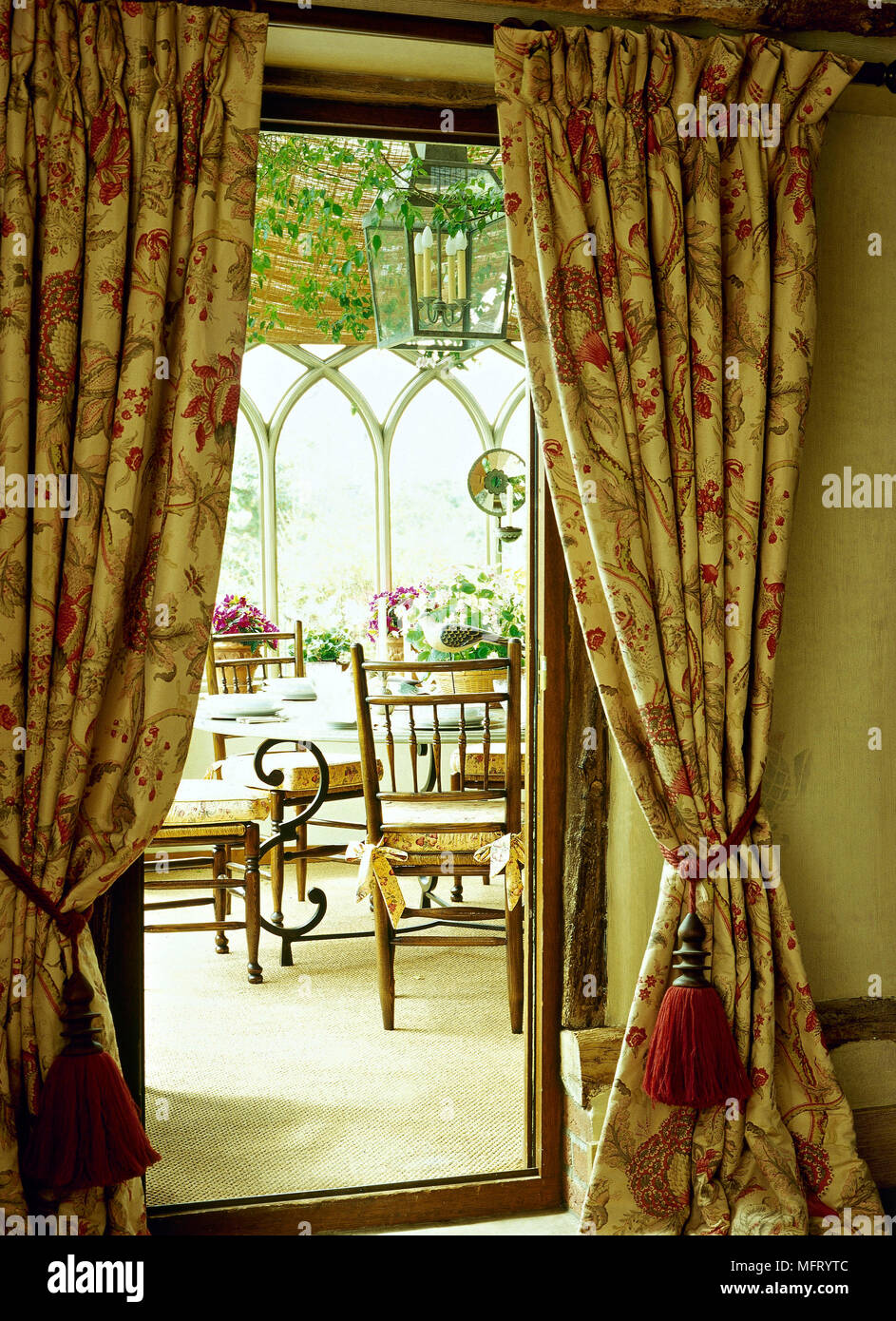 View Of Dining Room Through Door Curtains Wooden Chairs Set Table Lantern Light Windows Yellow Cushion Seats On Chairs Floral Pattern Curatins Either Stock Photo Alamy