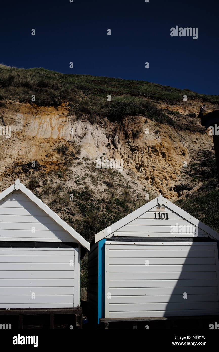 Exposed cliff geology at Bournemouth beach Dorset from the Eocene age shown here above the many beach huts along the beach front. - Stock Image