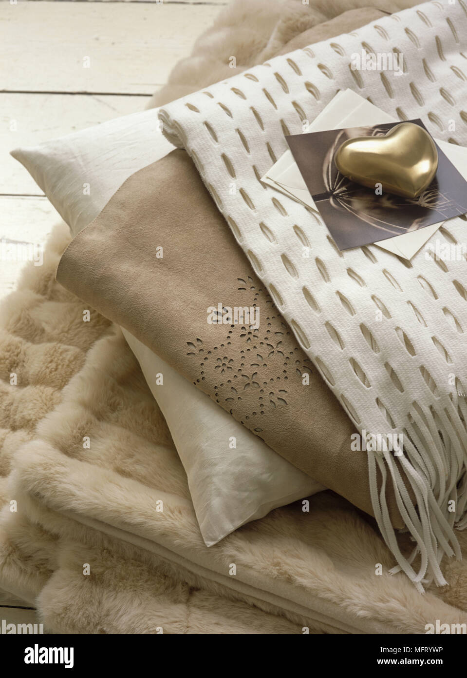 Fabrics and furry cushion covers in neutral colours - Stock Image