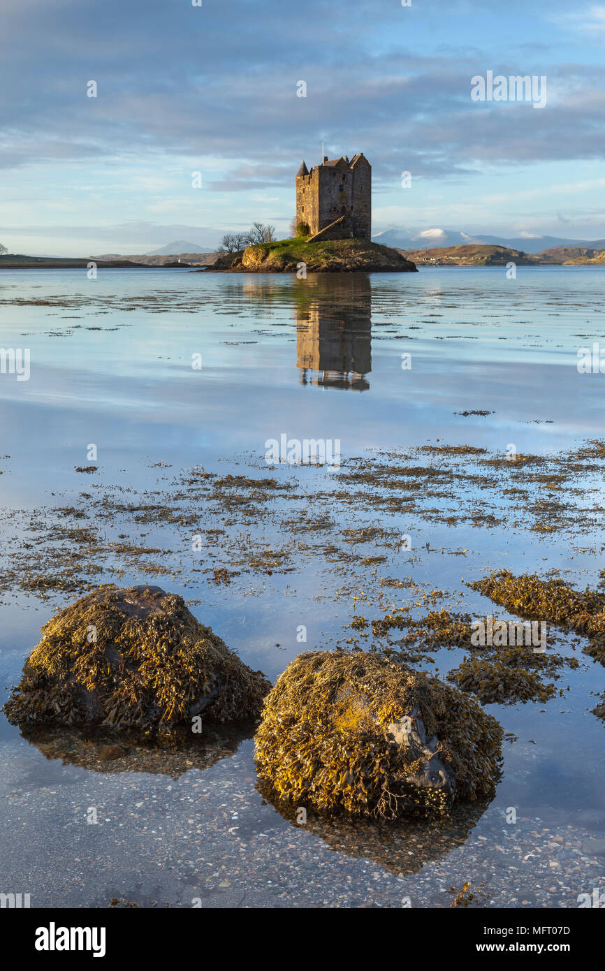 Castle Stalker at sunrise in winter. A castle surrounded by water on the west coast of Scotland, UK - Stock Image