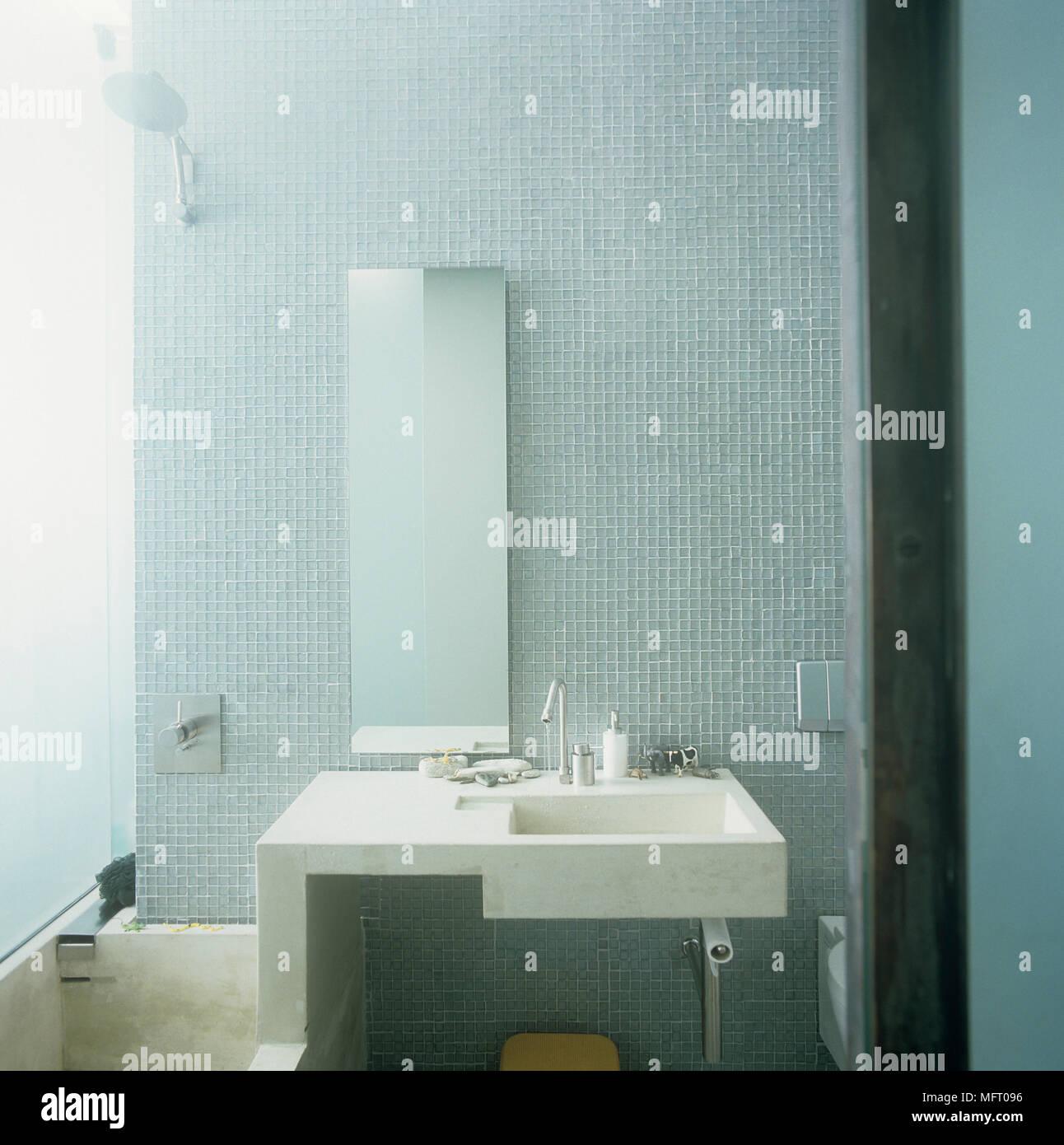 Wall mounted washbasin on tiled wall beneath mirror Stock Photo ...