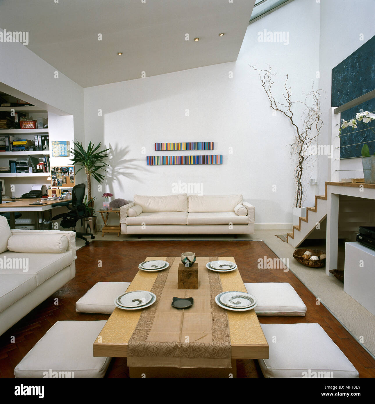 Modern open space with low wood table and floor cushions ...