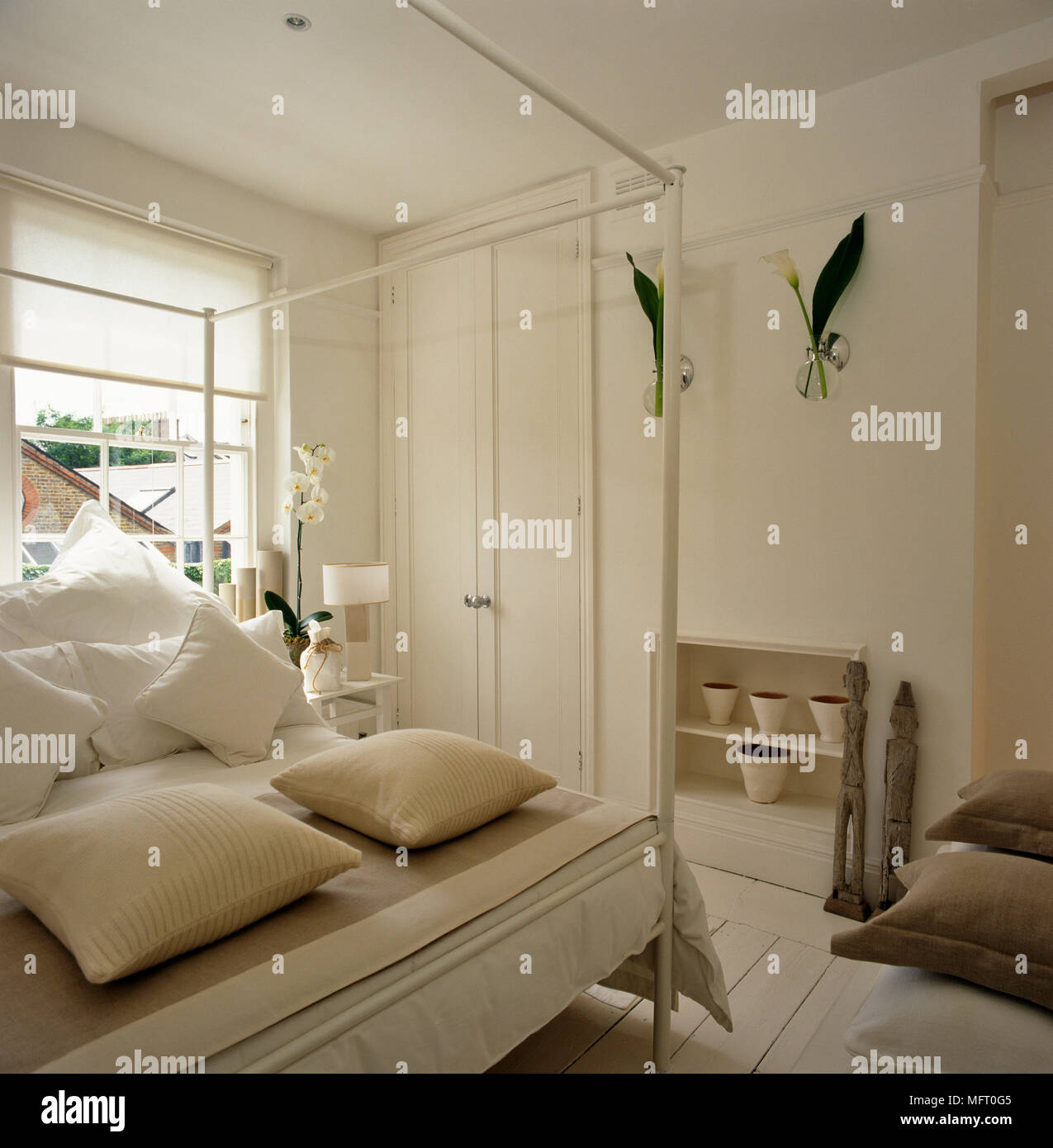 White Bedroom With Four Poster Bed And Cushions On Painted Floorboards Stock Photo Alamy