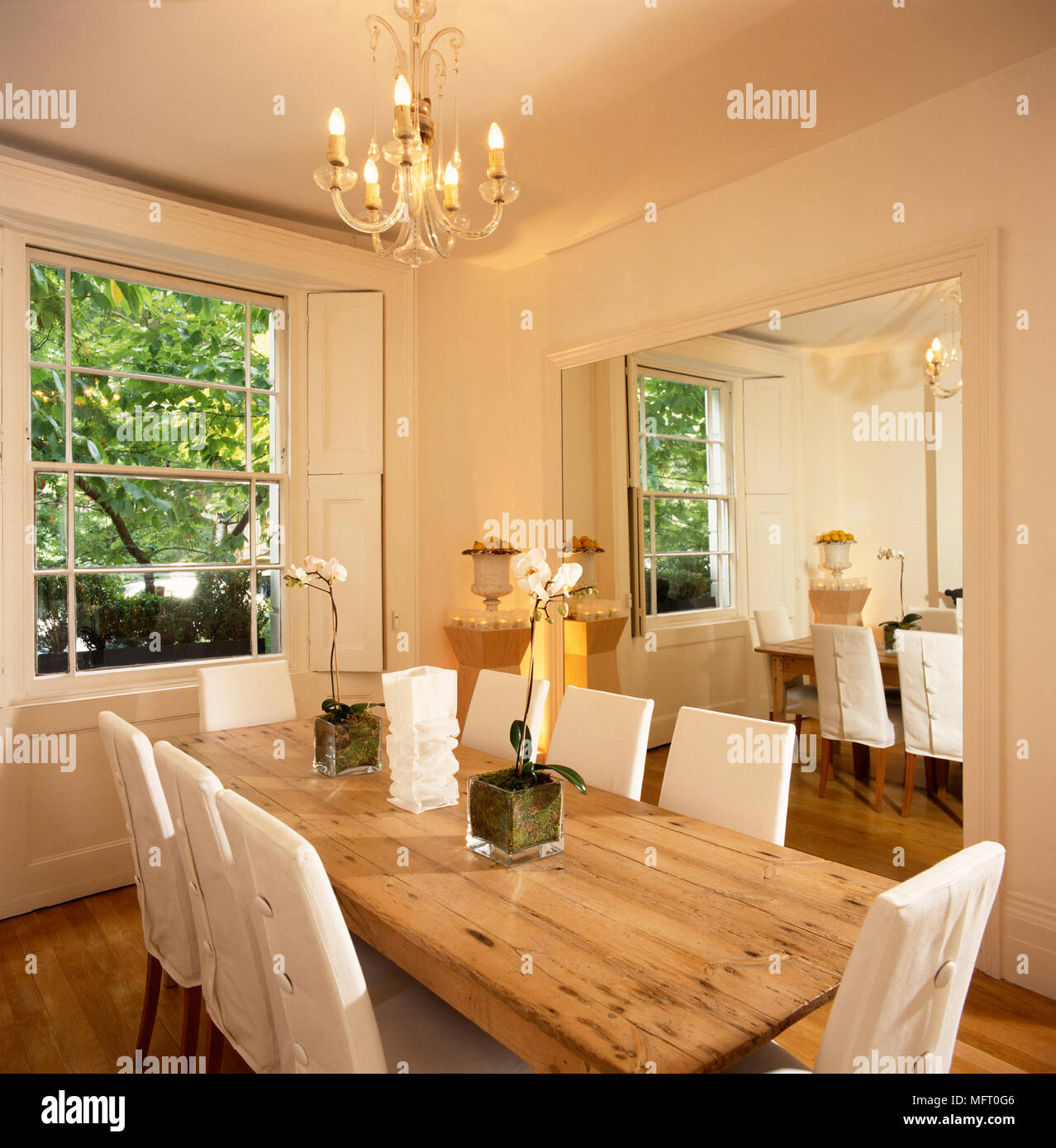 Simple elegant dining room, white walls, long pine table, chairs ...