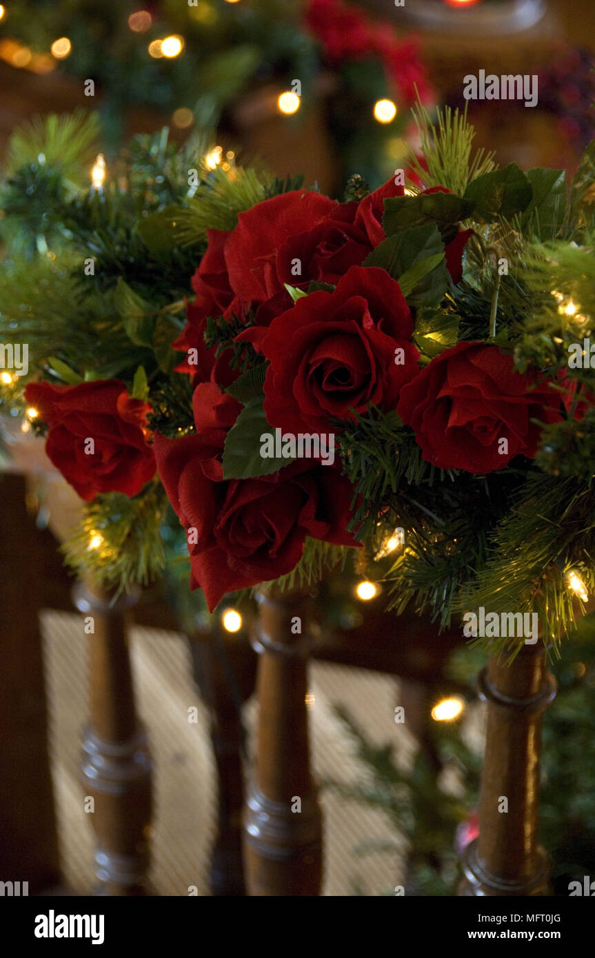 christmas garland of red flowers and foliage with fairy lights