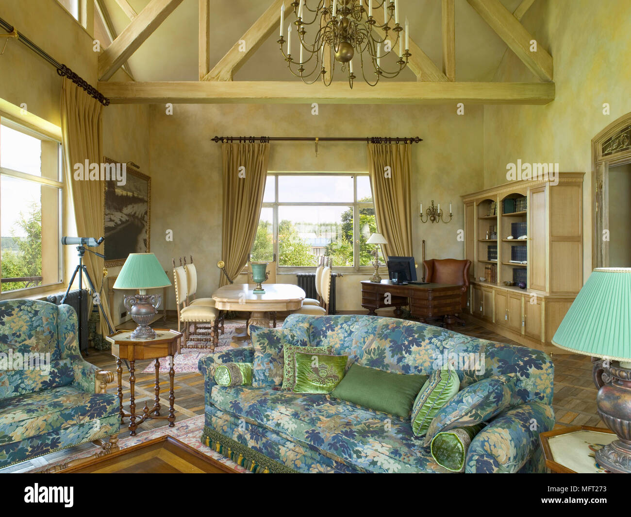 Sitting room with chandelier suspended from wooden beams above colourful settees with matching lampshades - Stock Image
