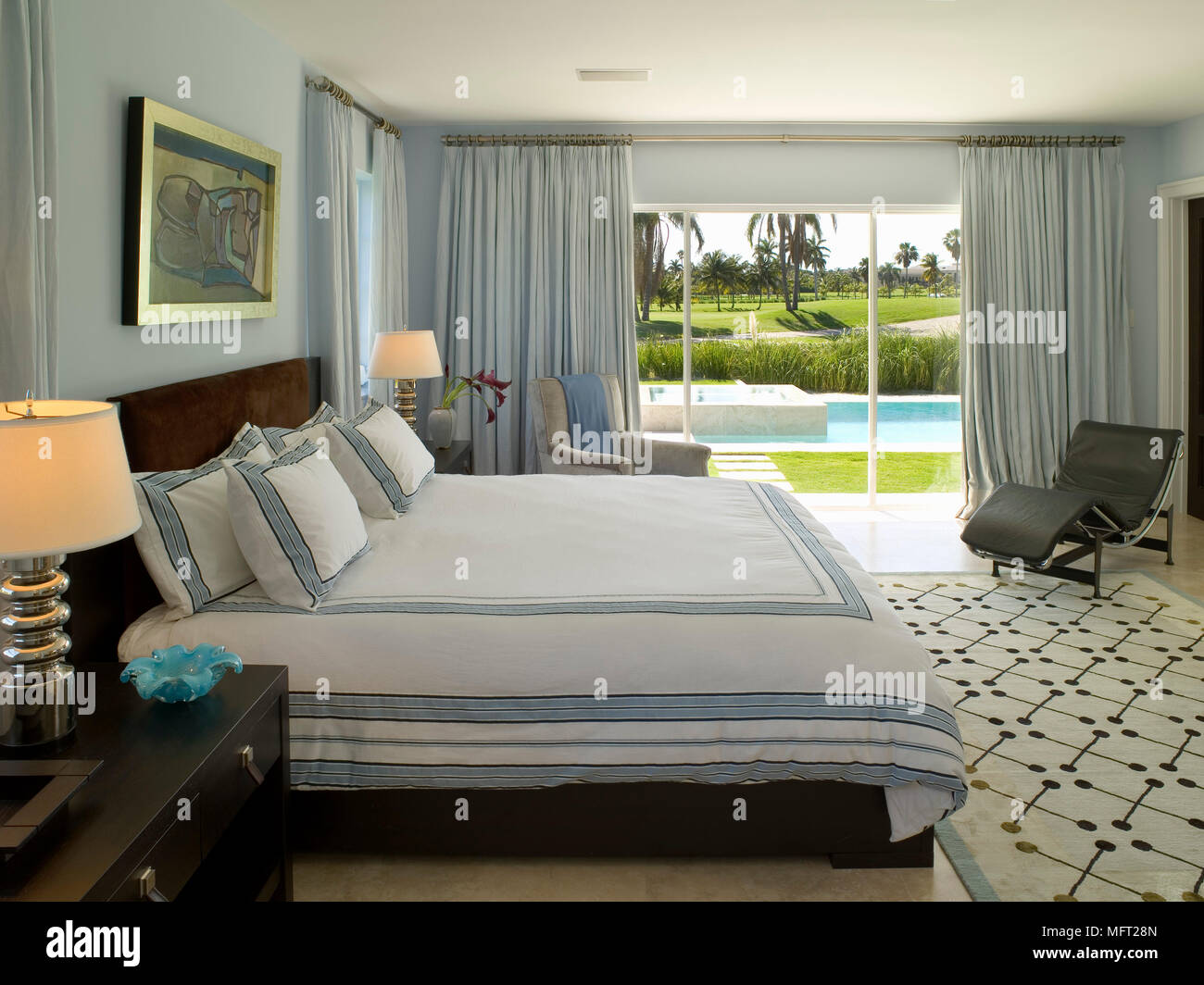 Bedroom With Framed Artwork Above Double Bed And Large Rug Leading To  Sliding Glass Doors With View On To Swimming Pool