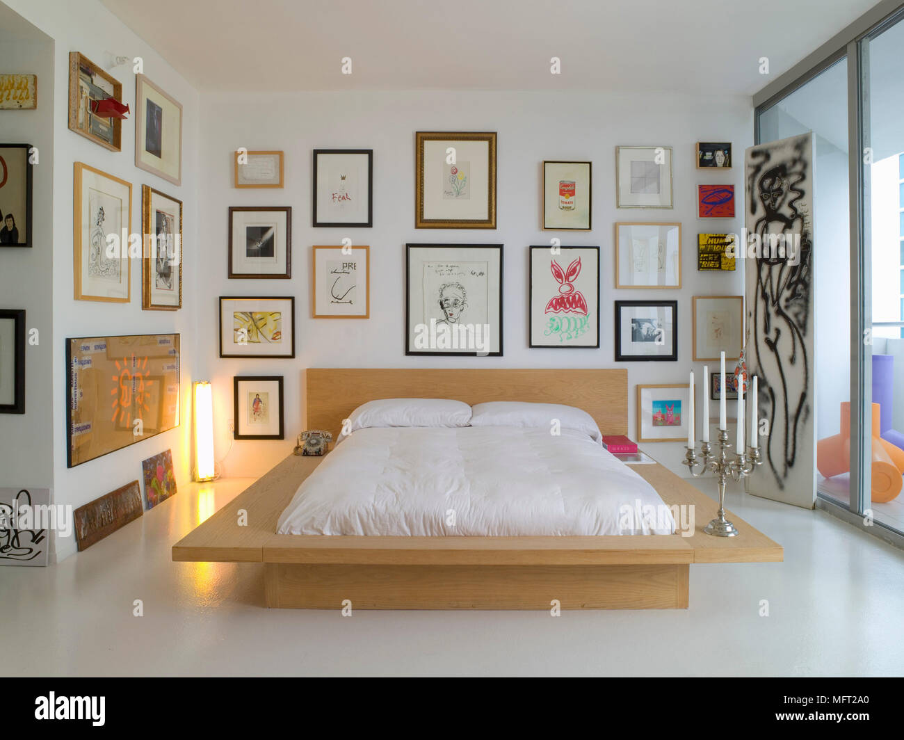 Bedroom With Low Bed With Wooden Base Surrounded By Framed Artwork Next To Large Window Stock Photo Alamy