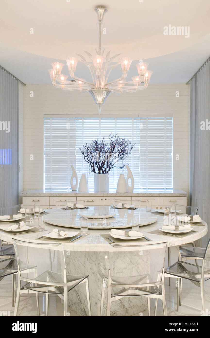 A Modern White Dining Room With A Chandelier Suspended Above An Circular Marble Table And Glass Chairs Stock Photo Alamy