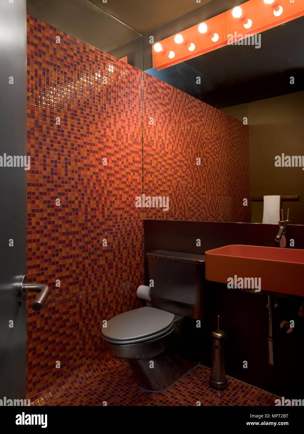 Gentil A View Through An Open Door Into A Modern, Red Bathroom, Tiled Wall,  Washbasin, Toilet, Bare Light Bulbs Set In Panel,