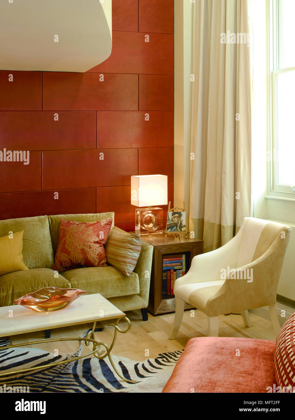 Modern Sitting Room Detail With Wood Floor, Red Tile Wall, Upholstered  Furnishings, And Sunny, Curtained Windows.