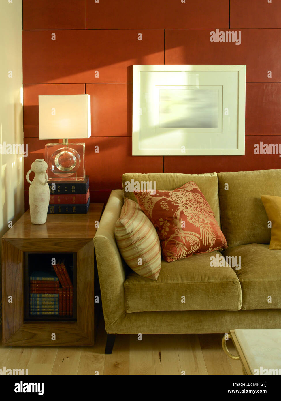 Modern sitting room detail with olive green sofa, red tile wall, and wooden side table. Stock Photo