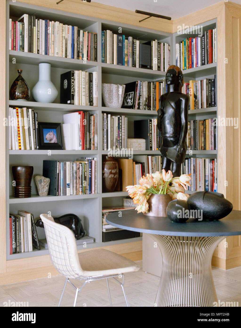 086aa28f64a5 Harry Bertoia dining chair at Warren Platner dining table in front of book  lined shelves