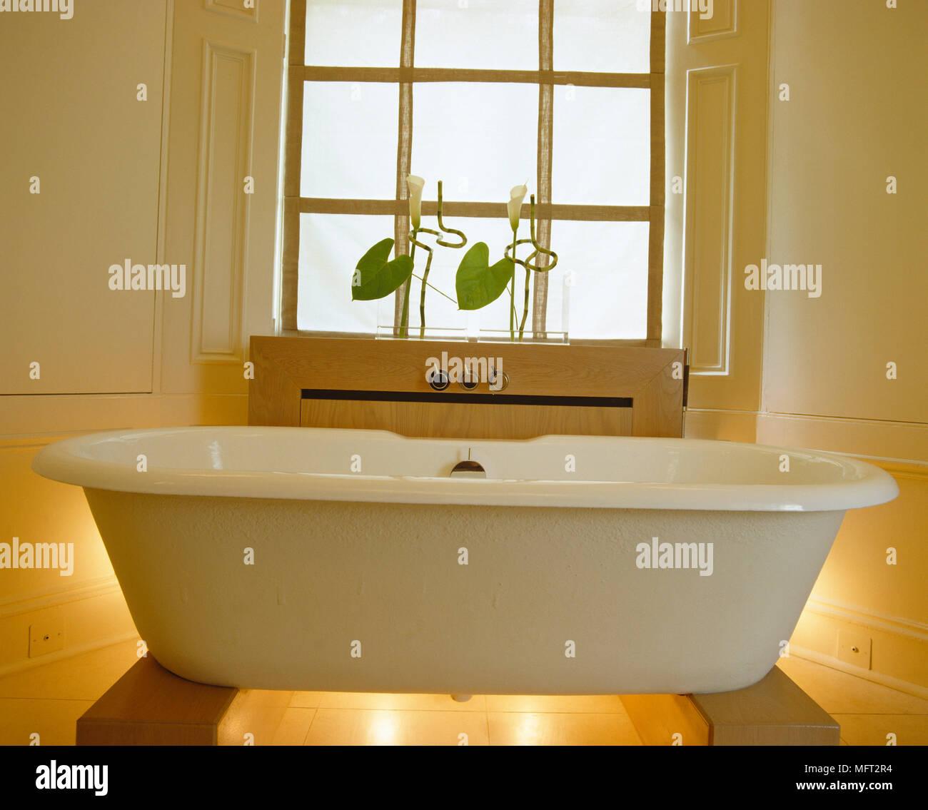 Freestanding roll top bath tub in front of window in yellow bathroom ...