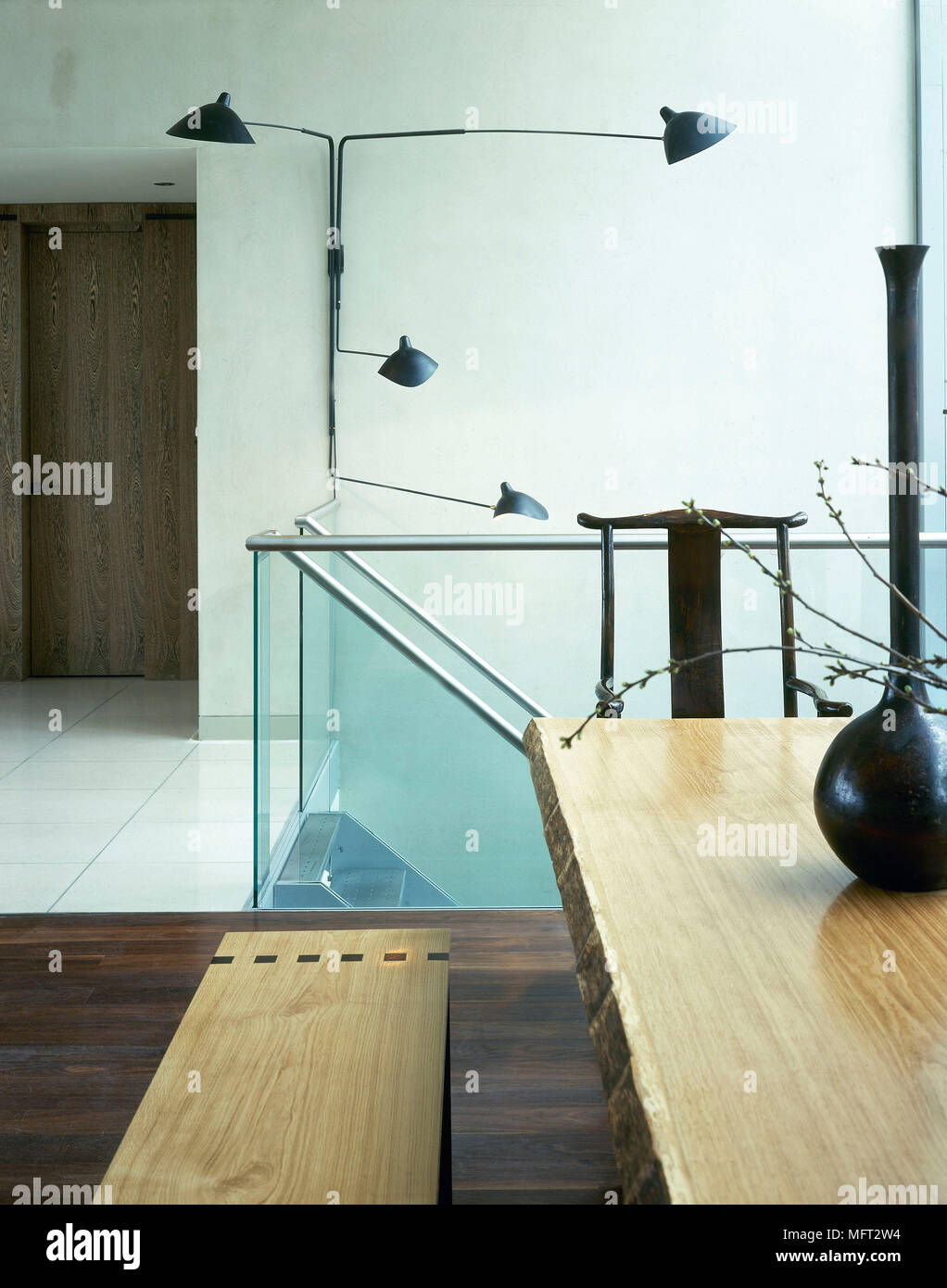 Wooden Bench Seat And Table Next To Staircase With Glass Panels In Contemporary Dining Room