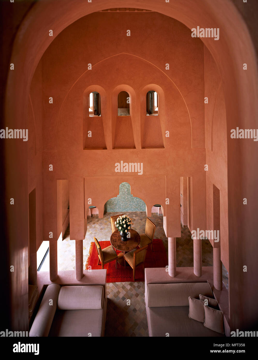 Moroccan terracotta dining room high arched ceiling round table chairs  interiors rooms ethnic influence warm colours arabian moorish archirectural de - Stock Image