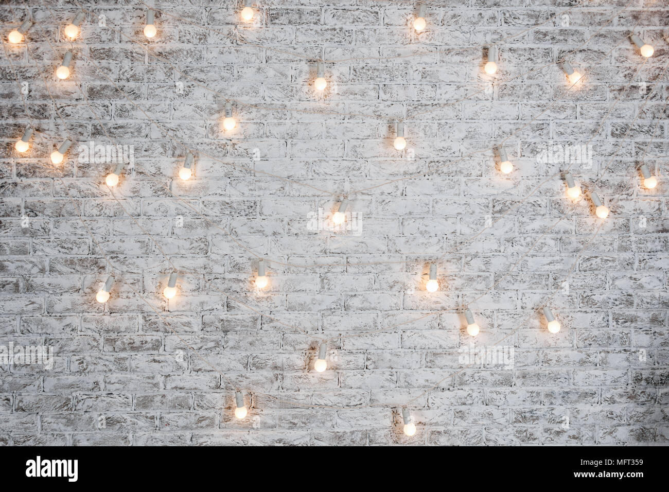 Great Light Bulbs On White Brick Background. Vintage Edison Light Bulbs Garland  In Loft Interior. Rustic Texture. Retro Whitewashed Old Brick Wall Surface.
