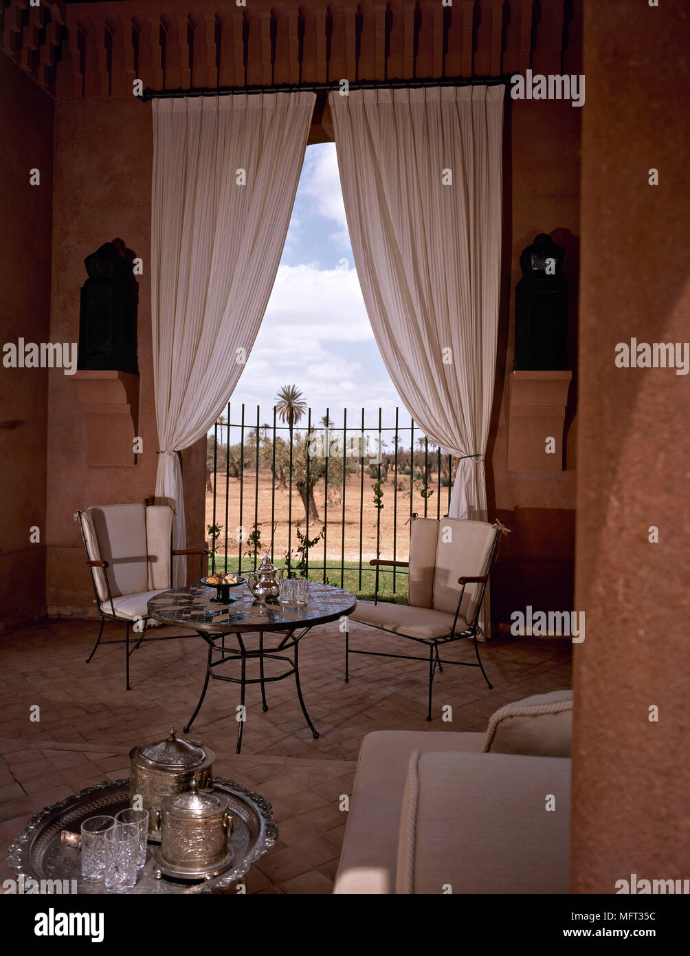 Moroccan sitting room detail metal round table chairs curtains  interiors rooms ethnic influence warm colours - Stock Image
