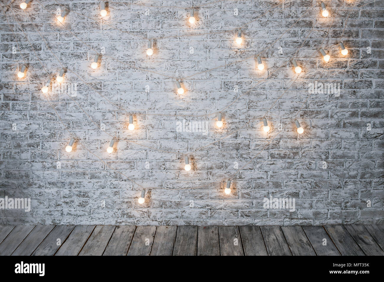 Light Bulbs On White Brick Background With Wooden Floor. Vintage Edison  Light Bulbs Garland In Loft Interior. Rustic Texture. Retro Whitewashed Old  Br