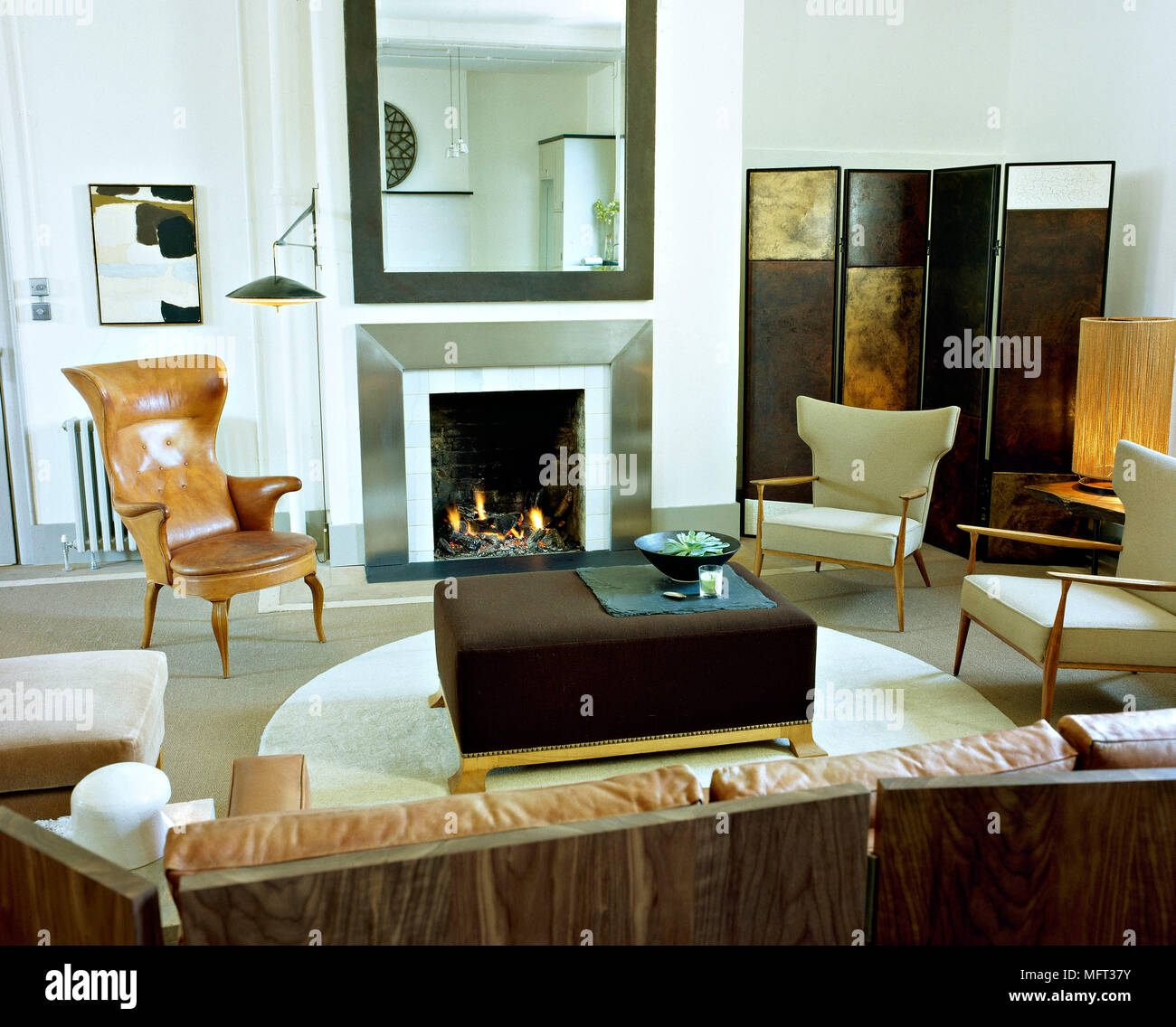 Modern sitting room fireplace lit fire metal surround brown leather ...
