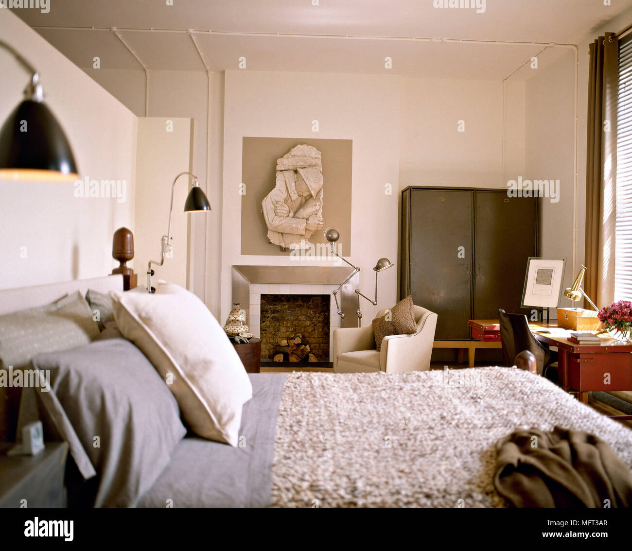Image of: Modern Neutral Bedroom Wooden Bed Textured Cover Fireplace Metal Surround Desk Chair Interiors Bedrooms Beds Modern Masculine Sitting Area Office Ar Stock Photo Alamy