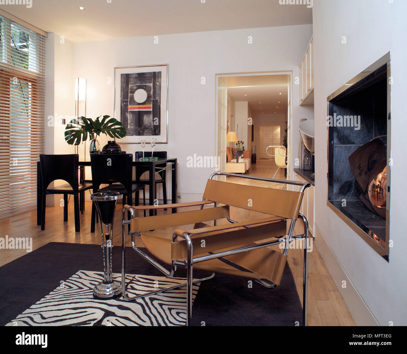 Marcel Breuer Wassily chrome and tan leather chair in front of recessed fireplace in contemporary open plan sitting room - Stock Image