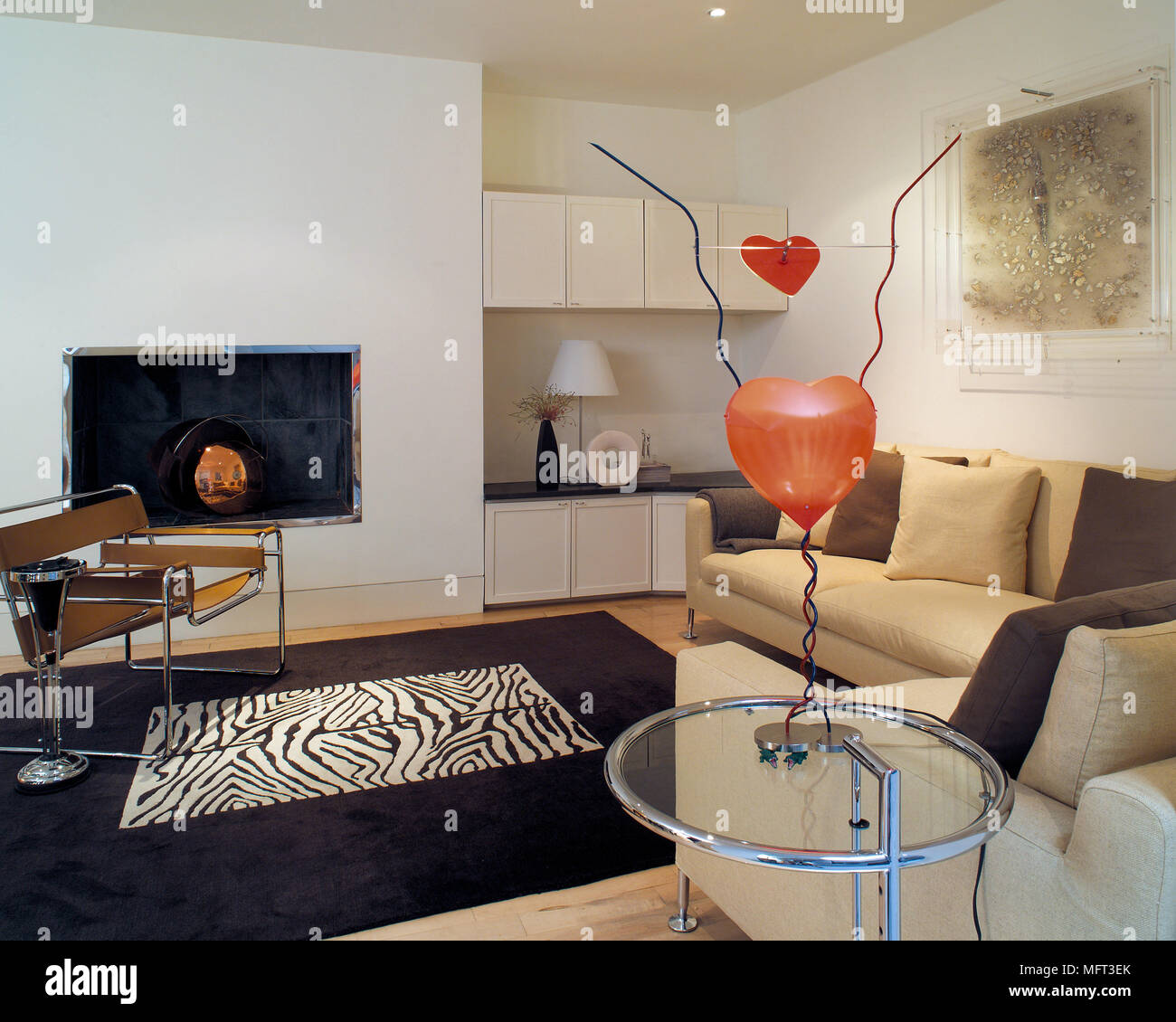 Marcel Breuer Wassily chrome and leather chair in front of contemporary recessed fireplace with Eileen Gray table in foreground - Stock Image