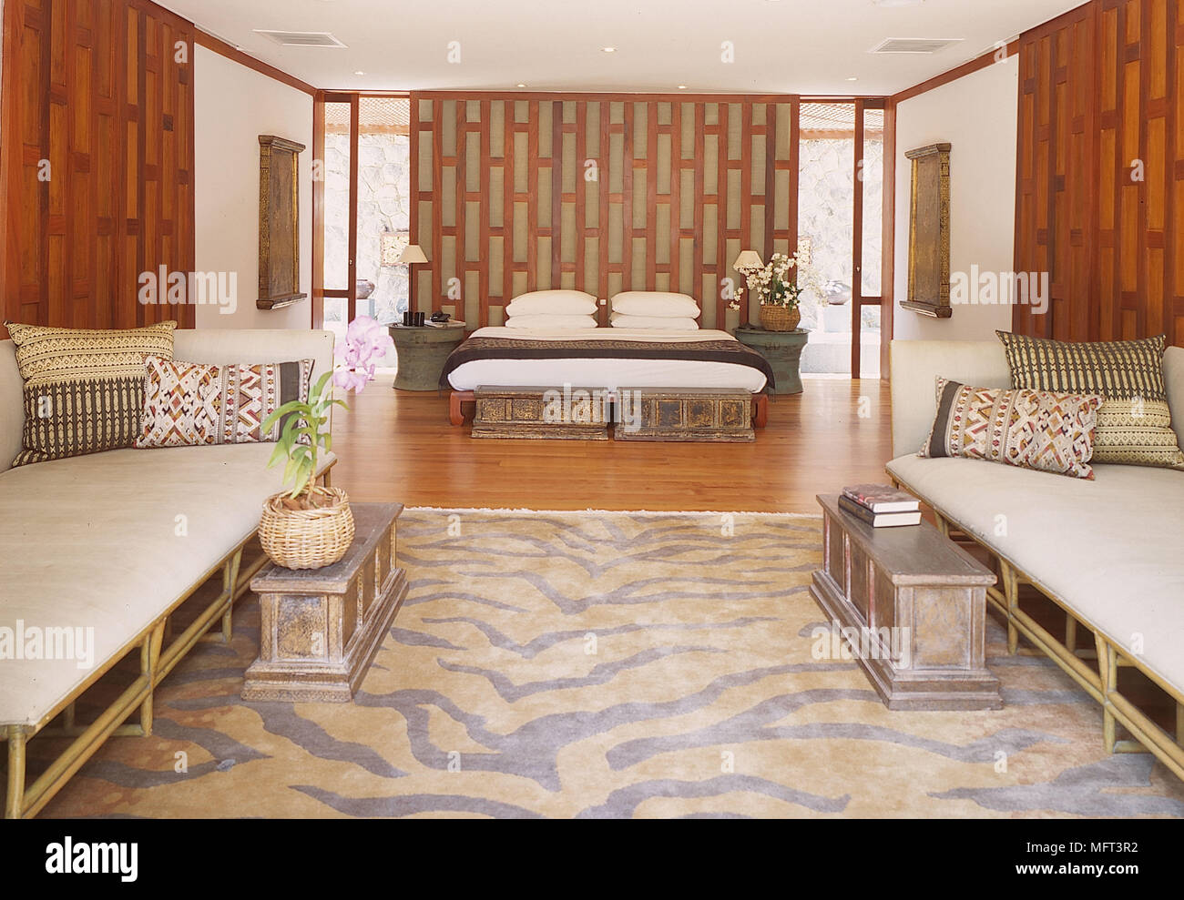 Bedroom white walls wood panelling flooring two sofas side ...