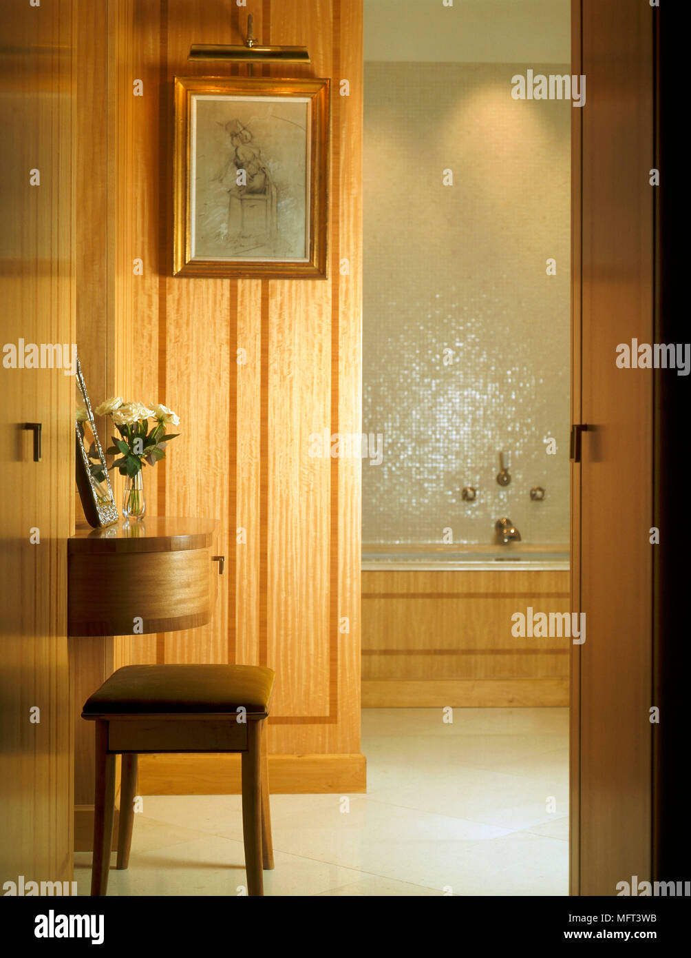 A View Through Open Door Into Of A Modern Bathroom With Wood Panelling Wall  Mounted Dressing Table Stool Bath