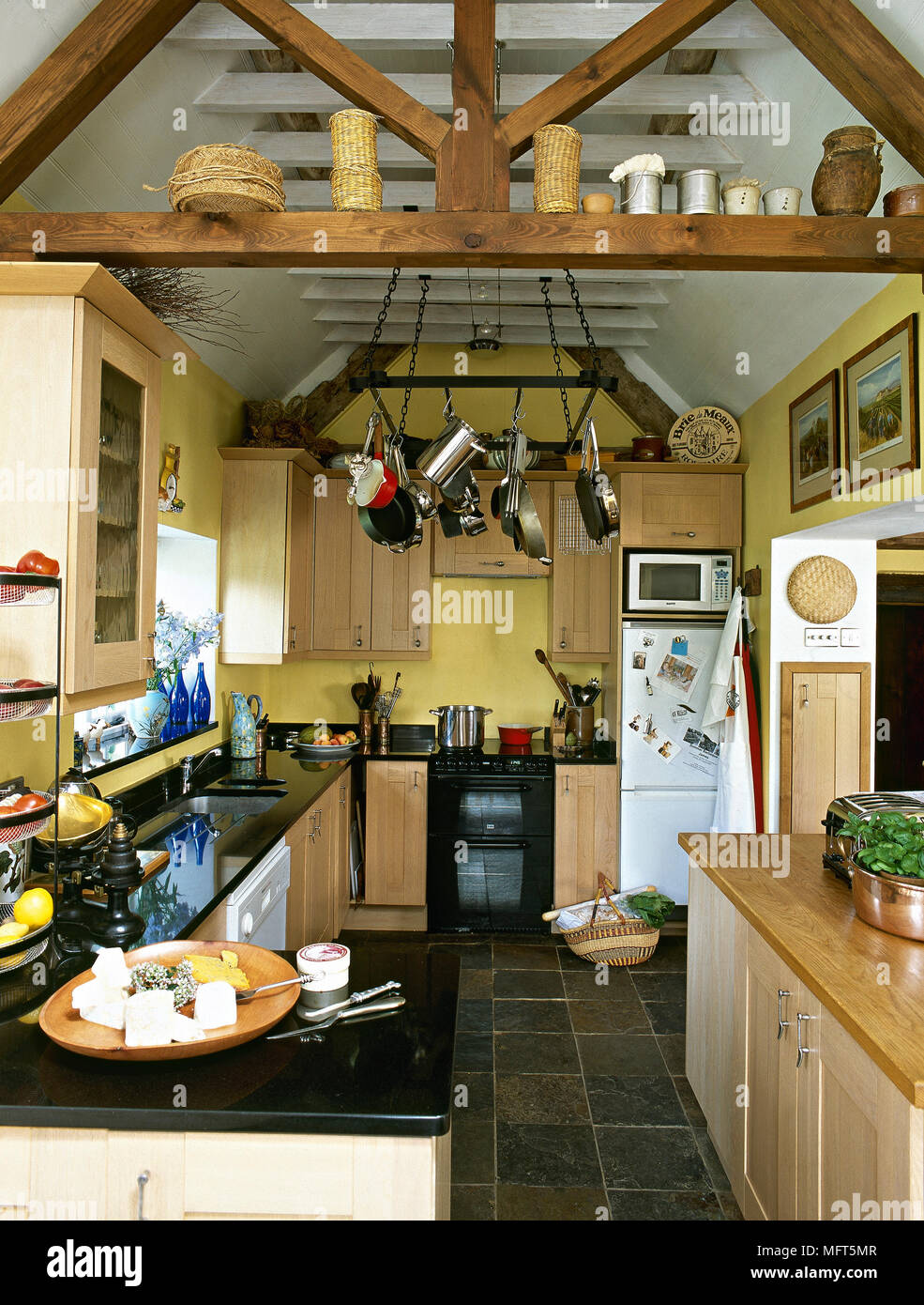 Kitchen With Exposed Ceiling Beams, Wooden Units With Granite Worktops And  A Slate Floor.