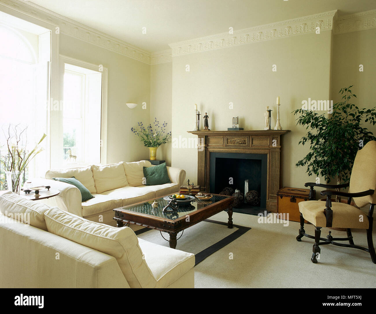 A Traditional Yellow Sitting Room With Carved Fireplace Cream