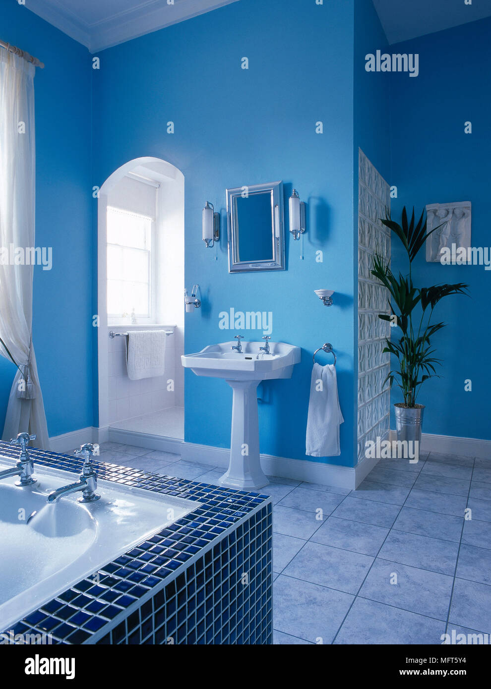 A modern bathroom with blue walls, bath with mosaic tiled surround ...