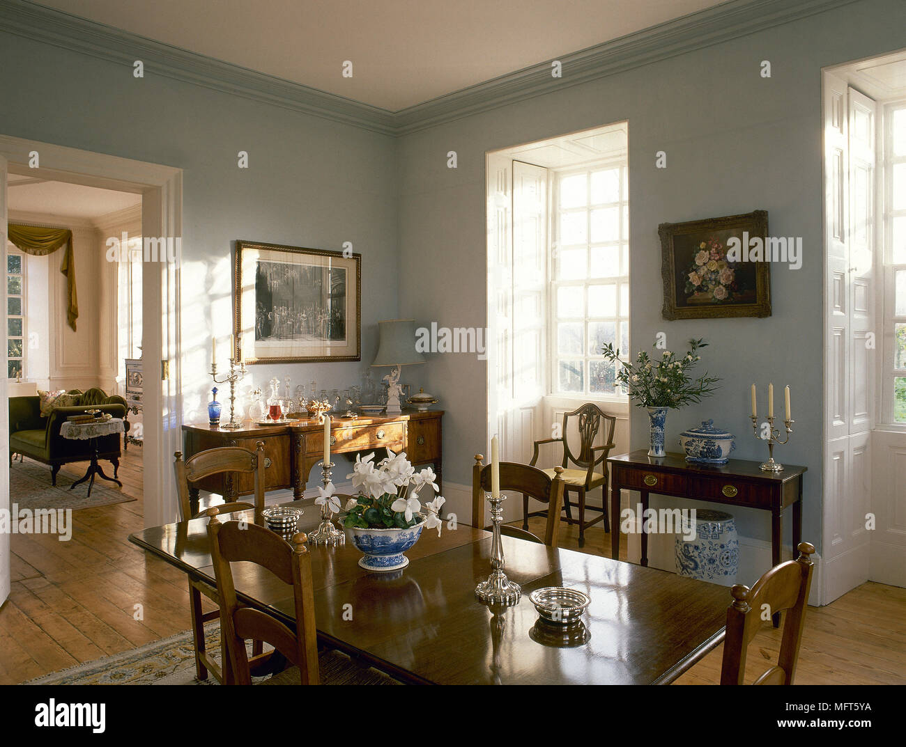 A Green County Dining Room With Polished Oak Table Chairs Side Board Bay Windows