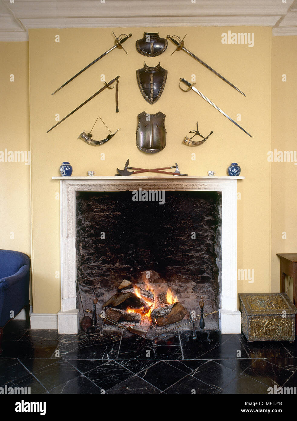 A detail of a yellow country sitting room, stone fireplace, slate ...