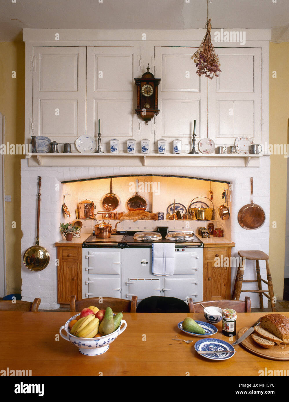 A Rustic, Country Kitchen With Farmhouse Table, White Aga In Recess, Copper  Pans,