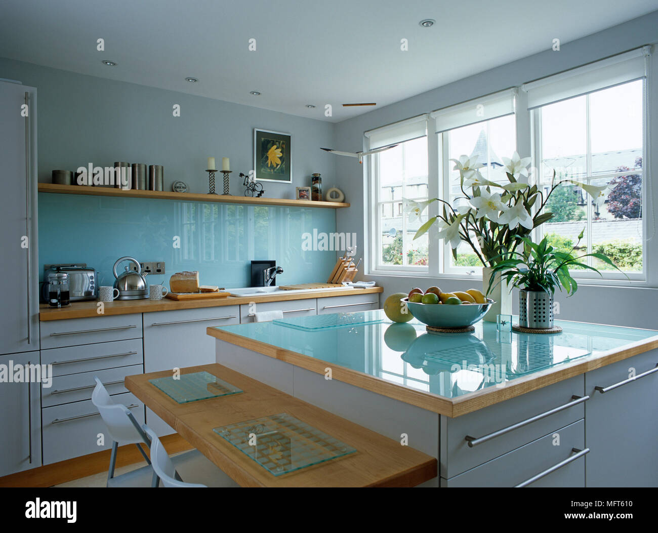 Central island unit with blue glass worktop and breakfast bar in ...
