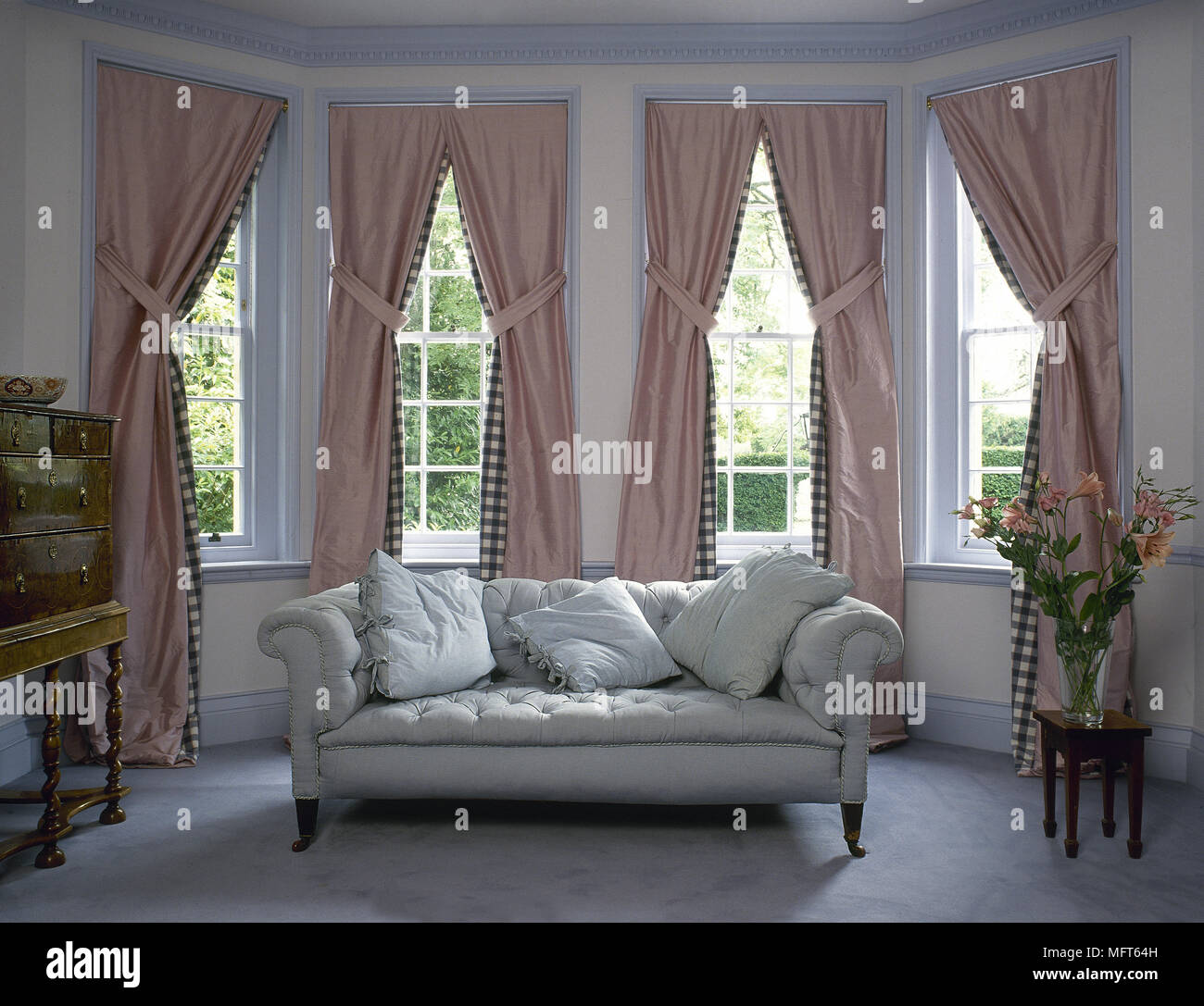 Upholstered Sofa Set In Georgian Bay Window Dressed With Pink Curtains,