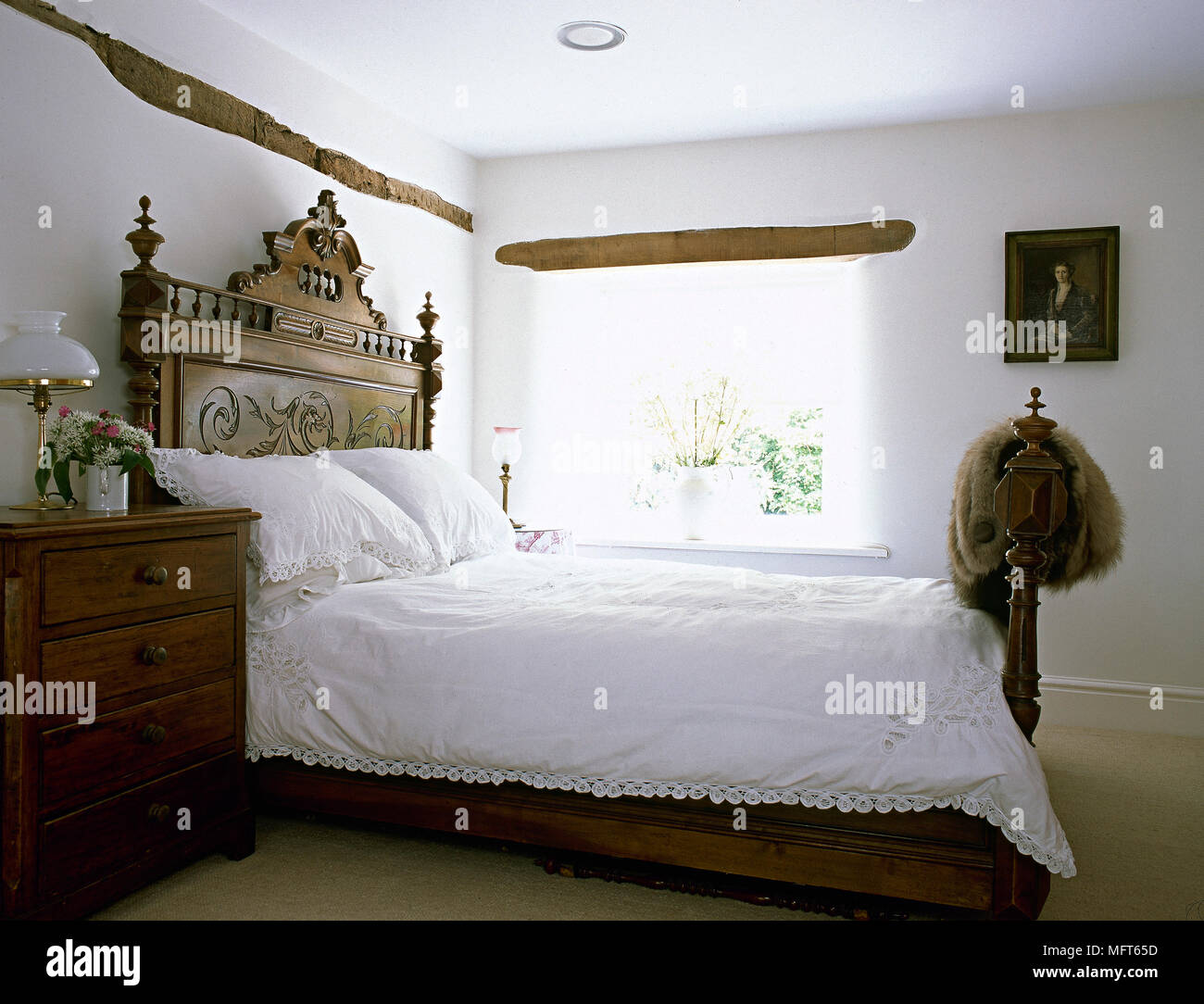 sports shoes c9e56 4c0b2 Double bed with ornately carved wooden headboard next to ...