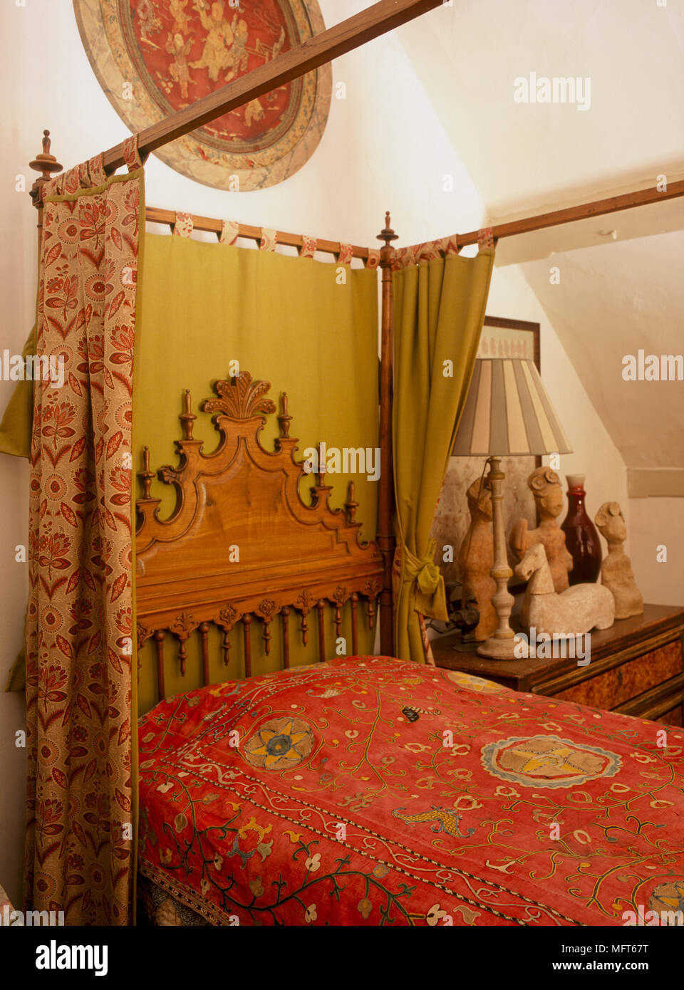 A Traditional Bedroom Four Poster Bed With Red Pattern Drapes And Bedcover Carved Wooden Headboard Bedside Table With Pottery Artifacts Stock Photo Alamy