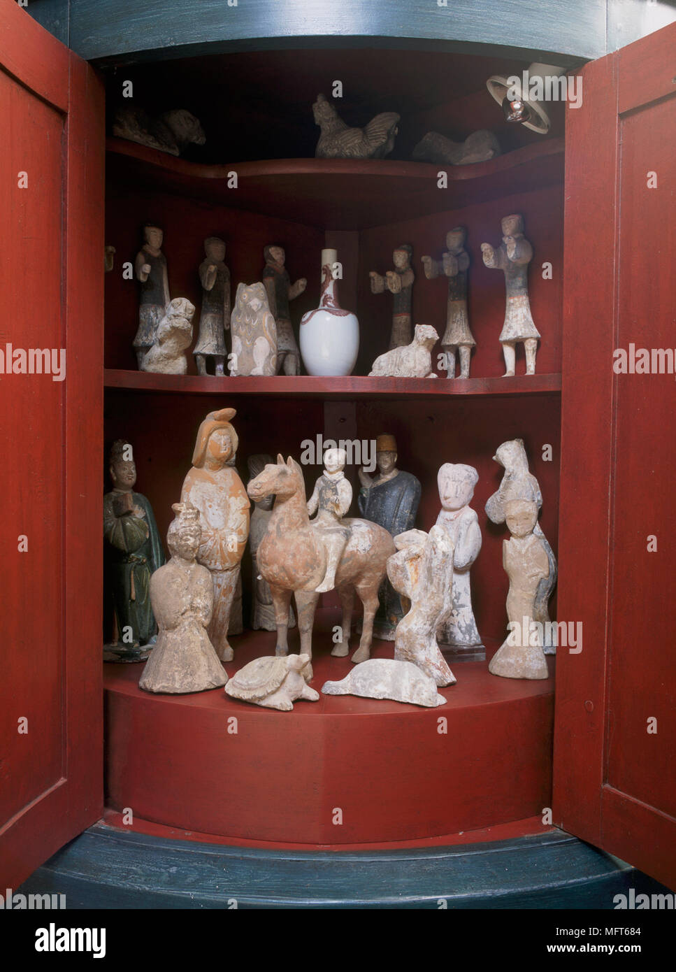 A Detail Of A Painted Red Display Cabinet With A Collection Of Pottery  Figurines, Statues And Antiquities