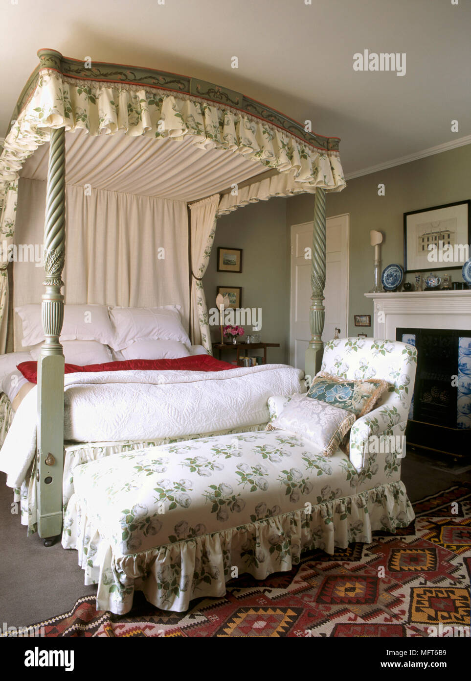 A Traditional Green Bedroom A Painted Four Poster Bed With Floral Fabric Canopy Upholstered Day Bed Fireplace Stock Photo Alamy