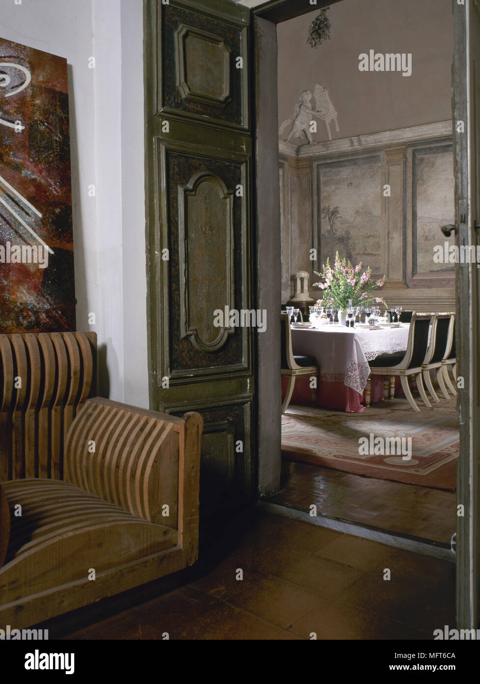 View Through The Panelled Doors Of A Seating Area To A Traditional Dining  Room With Painted Wall Murals And A Dining Table And Chairs.