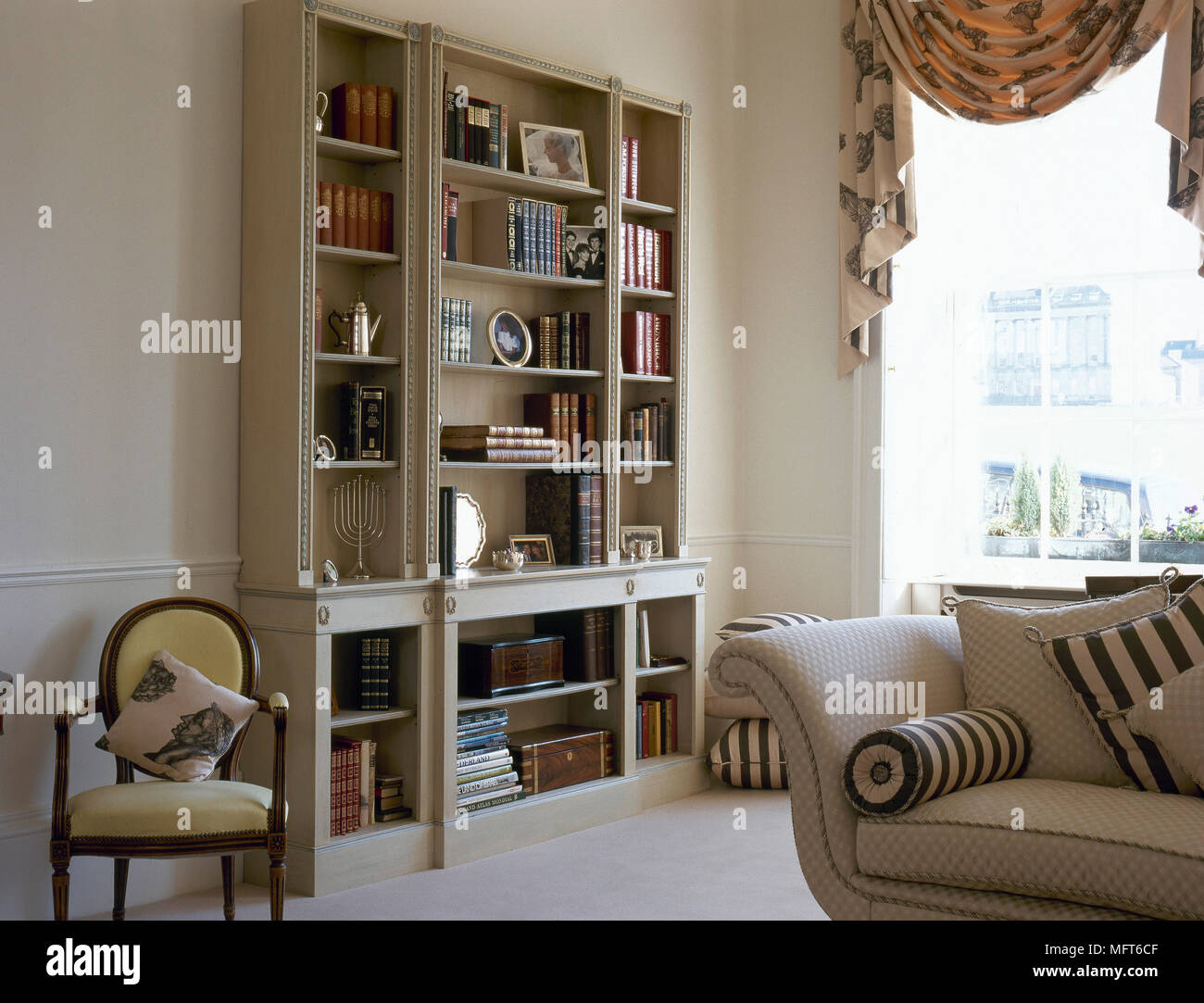 Traditional Sitting Room With A Bookshelf Upholstered Sofa And Sunny Window Swag Curtains