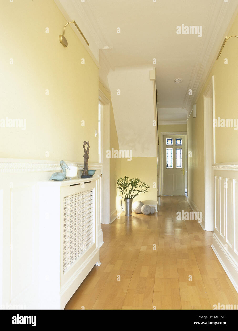 modern yellow hallway with wood floor covered radiator and front