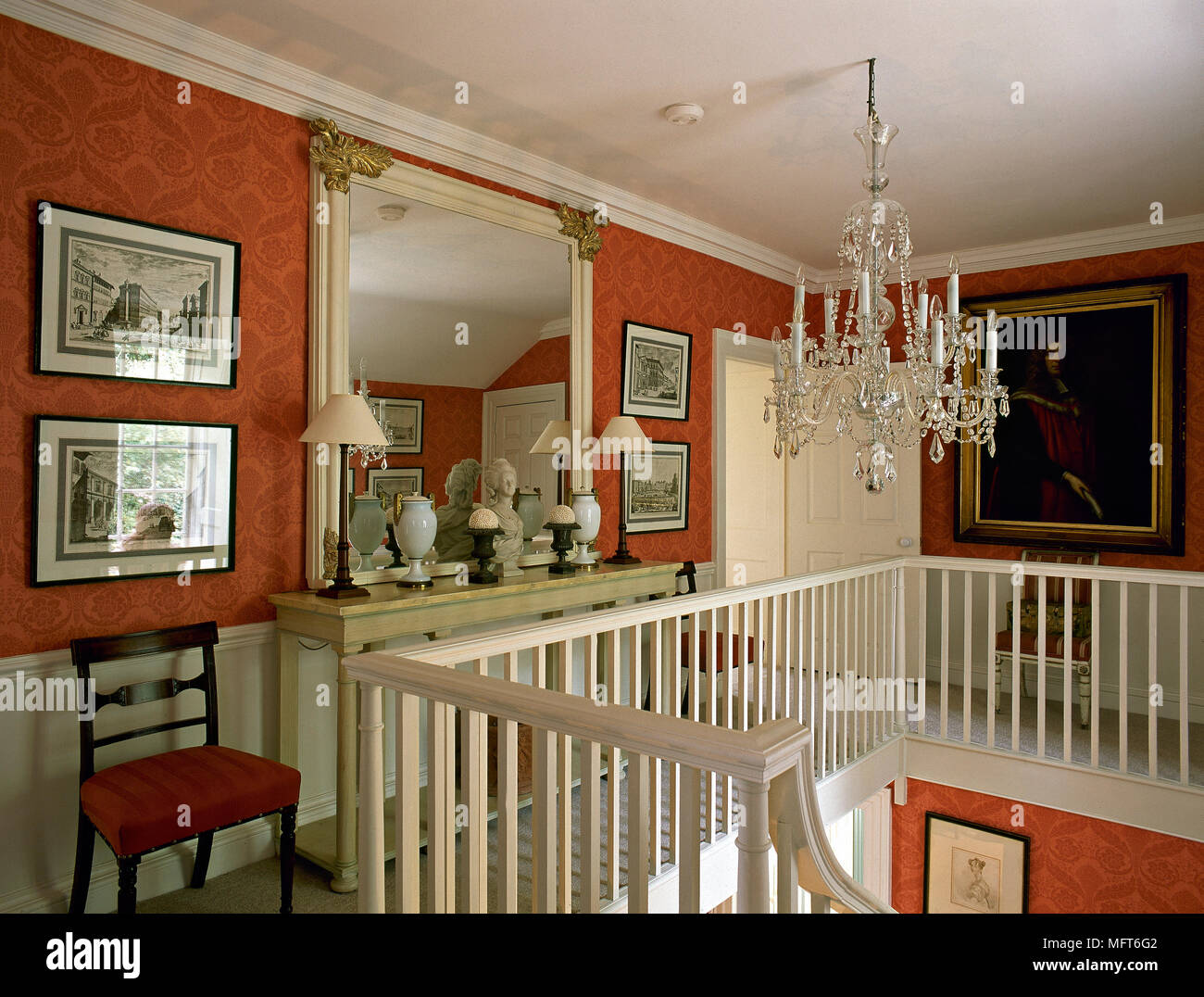 Traditional Second Floor Hallway With Red Wallpaper Crystal Chandelier Framed Mirror And Artwork A White Painted Banister