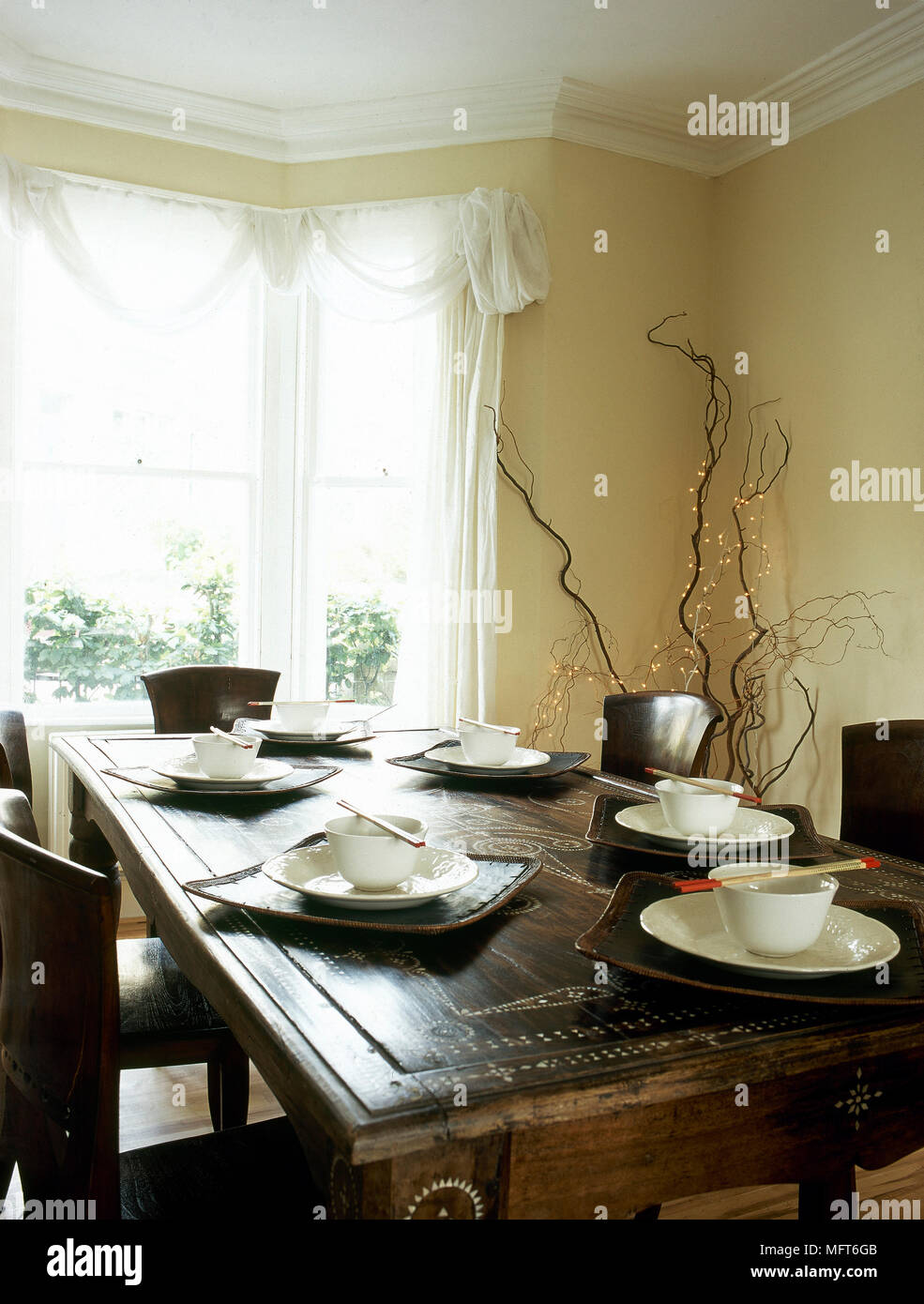 Modern, Country Dining Room With Inlaid Wooden Table And Chairs, Table  Settings, And Sheer Curtains Over A Bay Window.